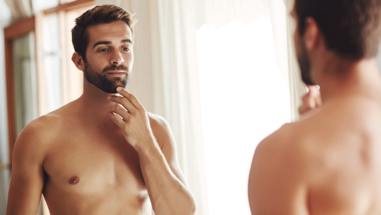 confident shirtless man looking in mirror