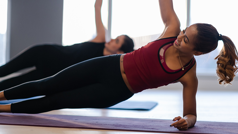 woman doing yoga with a friend