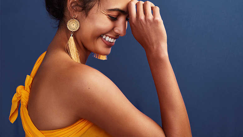 photo of a smiling woman, focused on her bare shoulder